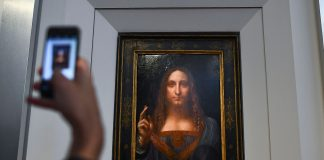 "A journalist takes photos of Leonardo da Vinci's ""Salvator Mundi"" after it was unveiled at Christie's in New York on October 10, 2017. One of fewer than twenty painting by Leonardo da Vinci and the only one in private hands, the Salvator Mundi will be offered in Christie's Evening Sale of Post-War and Contemporary Art on November 15, 2017, in New York, with an estimation in the region of 100 million US dollars. / AFP PHOTO / Jewel SAMAD / RESTRICTED TO EDITORIAL USE - MANDATORY MENTION OF THE ARTIST UPON PUBLICATION - TO ILLUSTRATE THE EVENT AS SPECIFIED IN THE CAPTION (Photo credit should read JEWEL SAMAD/AFP/Getty Images)"