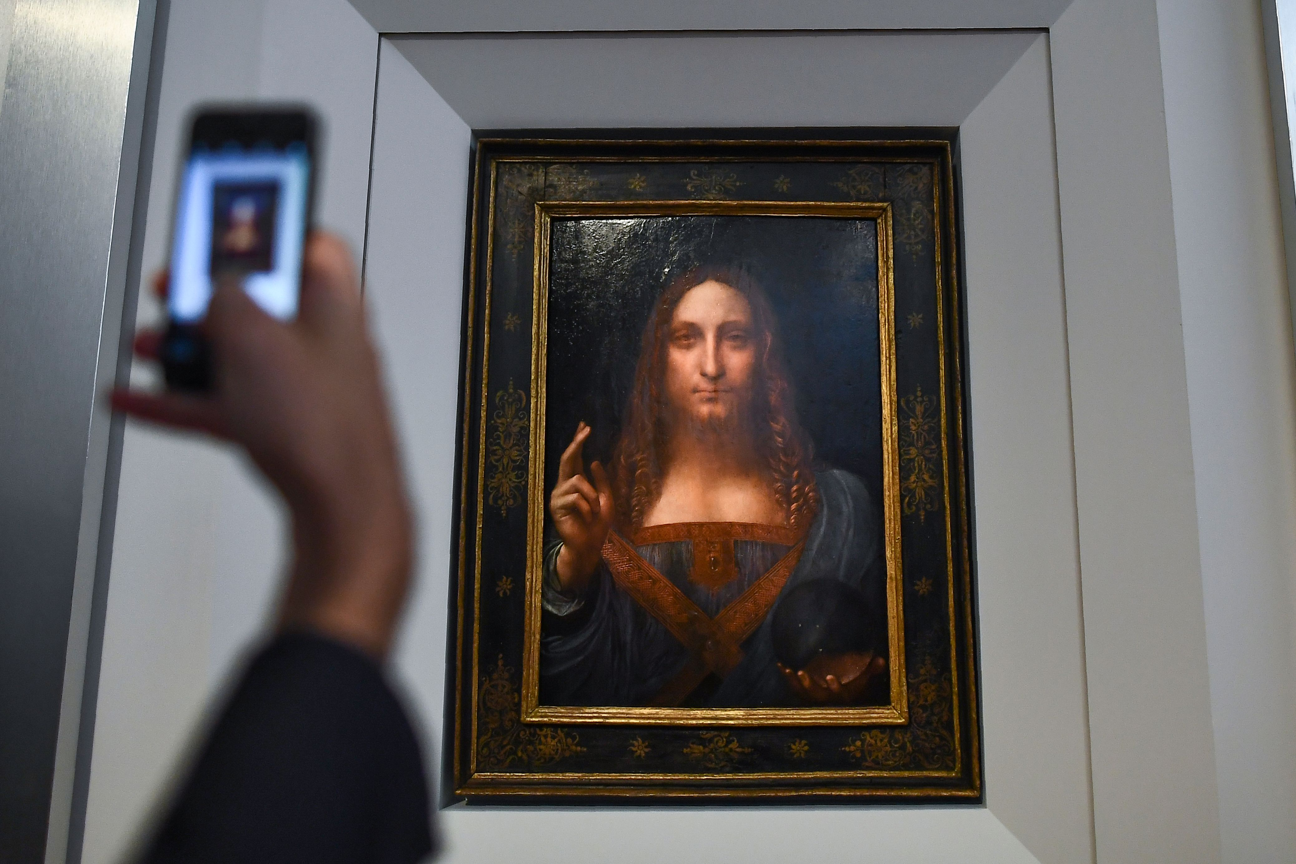 """A journalist takes photos of Leonardo da Vinci's """"Salvator Mundi"""" after it was unveiled at Christie's in New York on October 10, 2017. One of fewer than twenty painting by Leonardo da Vinci and the only one in private hands, the Salvator Mundi will be offered in Christie's Evening Sale of Post-War and Contemporary Art on November 15, 2017, in New York, with an estimation in the region of 100 million US dollars. / AFP PHOTO / Jewel SAMAD / RESTRICTED TO EDITORIAL USE - MANDATORY MENTION OF THE ARTIST UPON PUBLICATION - TO ILLUSTRATE THE EVENT AS SPECIFIED IN THE CAPTION (Photo credit should read JEWEL SAMAD/AFP/Getty Images)"""